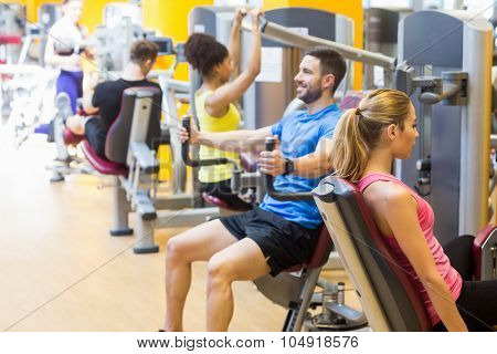 Fit people using weights machines at the gym