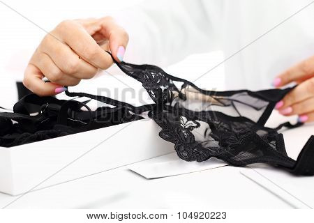 Hands women packing lacy underwear in a box