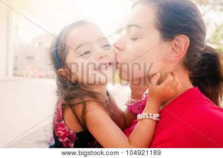 Young Mother Kissing Her Daughter