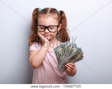 Serious Cute Kid In Glasses Looking On Dollars In Hand And Thinking How To Spend Money
