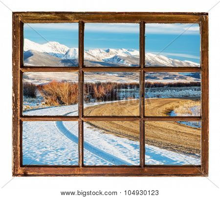 travel concept - a view of windy  road and snowy mountains  through vintage, grunge, sash window with dirty glass  - Medicine Bow Mountains, Colorado