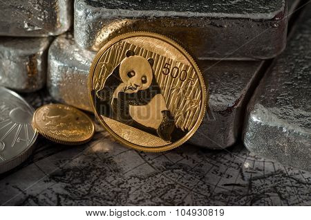 Chinese Gold Panda Coin Infront Of Silver Bars On Map