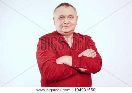 Aged man wearing red shirt standing with crossed arms and smiling against white background - retirement concept