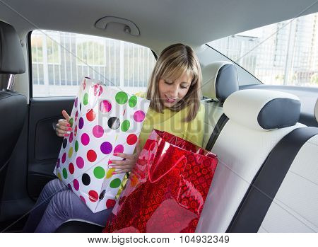 Woman Sitting In Car With Shopping Bags