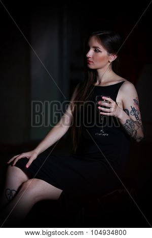 Young woman with glass of red wine in the room