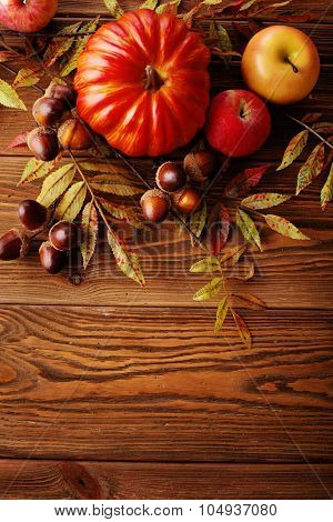 colorful leaves, pumpkin, apples on wooden background
