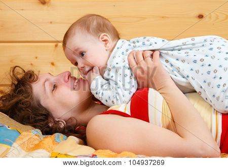 Mother Lying On The Bed With Little Baby