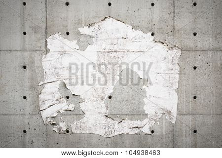 Old billboard and a grey wall with torn poster