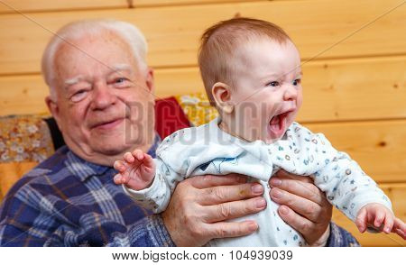 Happy Senior Man With Toddler In His Hands