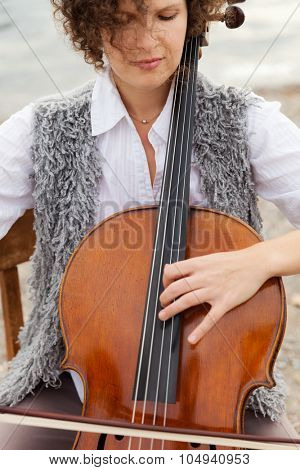 woman playing the cello at the seaside