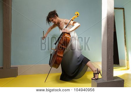 Attractive woman in evening dress playing cello, interior