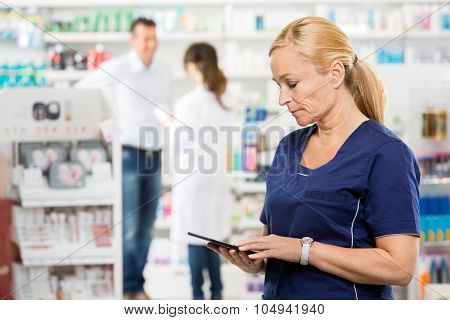 Female assistant holding digital tablet while pharmacist and customer standing in background at pharmacy