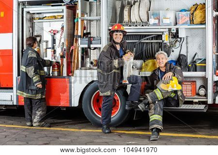 Portrait of confident male firefighters by truck at fire station