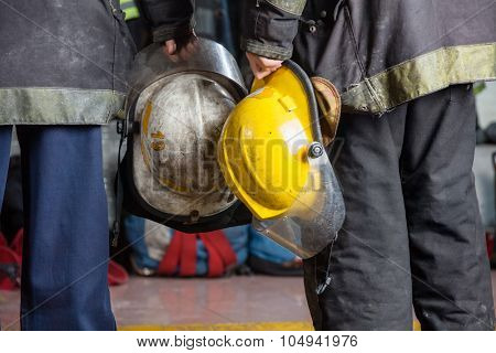 Midsection rear view of firemen holding helmets at fire station