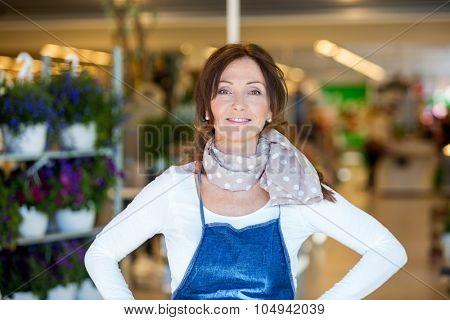 Portrait of confident mid adult female florist in shop