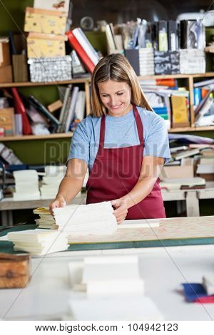 Happy mid adult woman stacking papers at table in factory