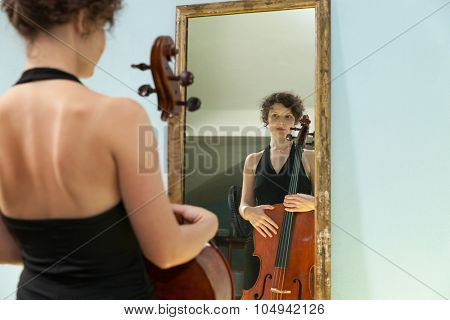 beautiful woman with cello looking into a mirror at herself