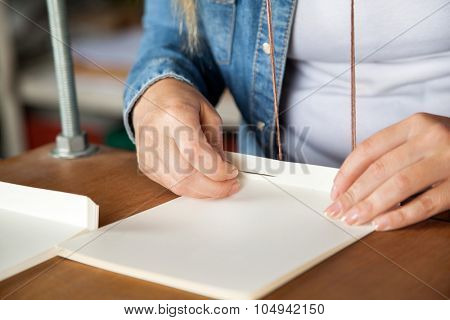 Closeup of female worker inserting needle in paper at factory