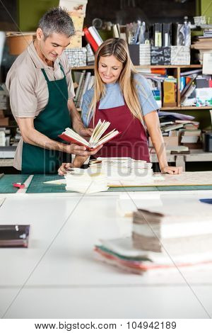 Smiling male and female workers analyzing notebook together in factory