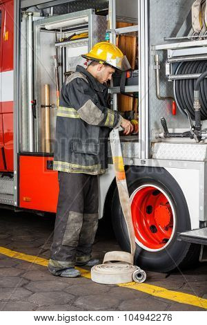 Full length of male firefighter fixing water hose in truck at fire station
