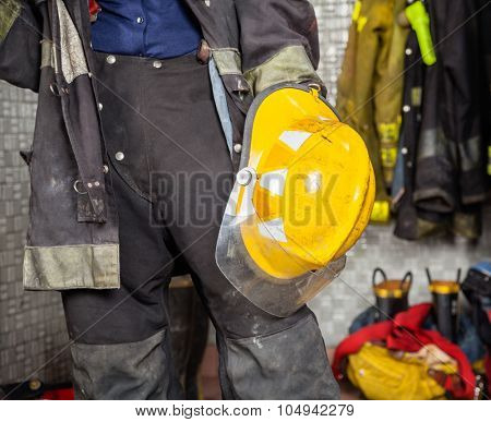Midsection of firewoman holding helmet while standing at fire station