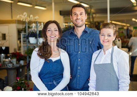 Portrait of happy man with salesgirls in flower shop
