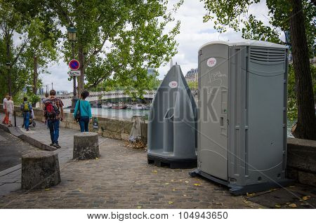 People walk by public toilet facilities on Quai d'Orleans