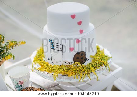 Funny wedding cake from mastic with a cup of milk and cookies.