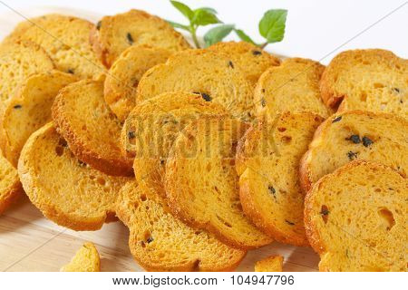 close up of bread rusks with black olives on wooden cutting board
