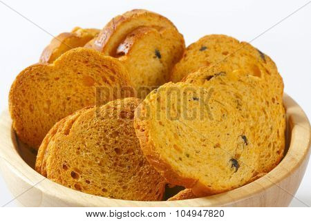 detail of bread rusks with black olives in wooden bowl