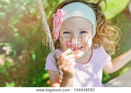 happy child girl smells flower on swing in summer garden