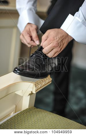 Best man getting ready for a special day. A groom putting on shoes as he gets dressed in formal wear