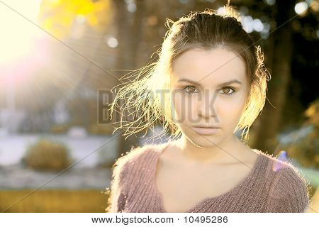 A Beautiful Brunette Stands In The Autumn Sun Light