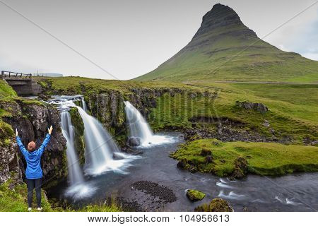 Threaded full-flowing waterfall Kirkjufell Foss on the grassy mountains. Middle-aged woman tourist admires the beauty of nature