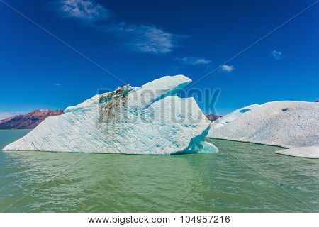 The huge white-blue iceberg drifts from coastal glacier in warm summer day. Argentina Patagonia, Lake Viedma