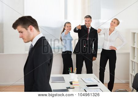 Businesspeople Teasing Businessman In Office