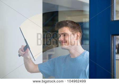 Worker Cleaning Glass With Squeegee