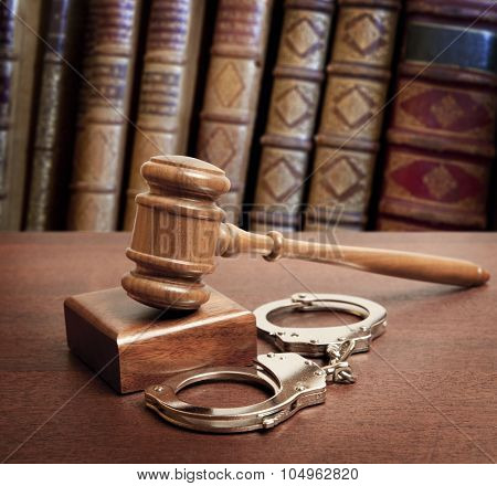 Gavel and handcuffs on book background