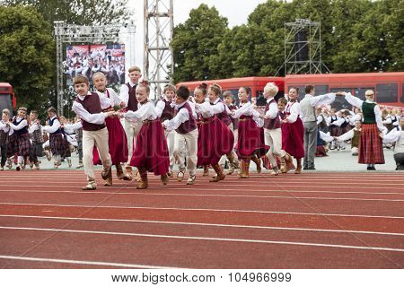 RIGA, LATVIA - JULY 11, 2015: Dancers in traditional costumes perform at the Grand Folk dance concert of Latvian Youth Song and Dance Festival in the Daugava Stadium.