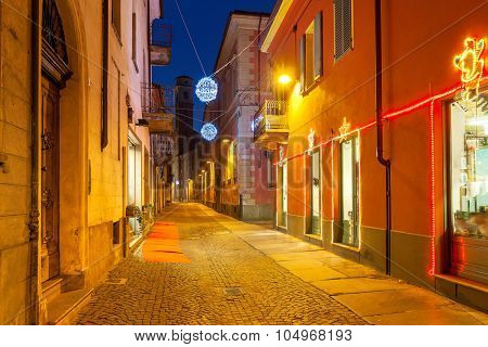 Narrow cobbled street between houses illuminated and decorated for Christmas holidays in town of Alba, Piedmont, Northern Italy.