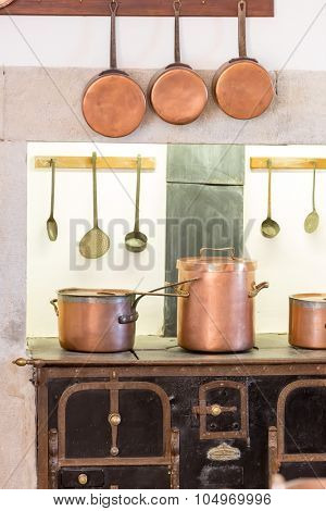 Retro kitchen interior with old pans, pot on the furnace