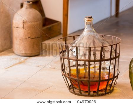 Carboy with some beverage stands on the floor in the kitchen