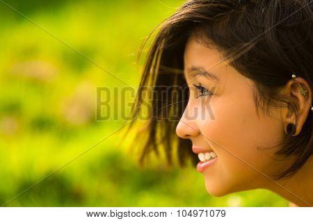 Headshot profile pretty teenage hispanic girl with half short hair and green blurry background