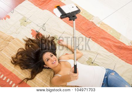 Pretty brunette wearing denim jeans and white top lying down on bedsheets hair spread out, holding s