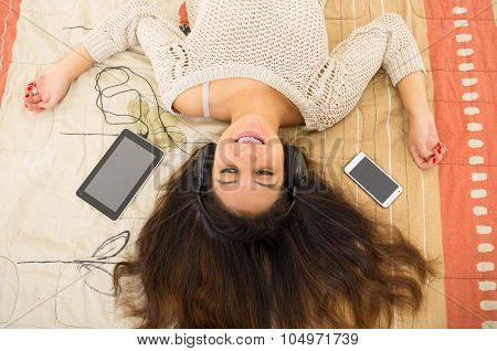 Pretty brunette wearing denim jeans white top lying down on bedsheets daydreaming with smartphone an