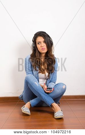Pretty brunette wearing denim jeans and shirt plus white top sitting on wooden surface her back agai