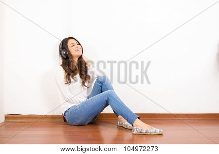 Pretty brunette wearing denim jeans and white top sitting on wooden surface her back against wall, b
