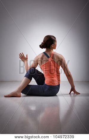 Beautiful sporty fit yogini woman practices yoga asana ardha matsyendrasana - half spinal twist pose
