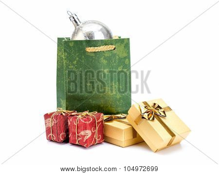 Green paper christmas shopping bag with silver christmas ball and present boxes shot on white background