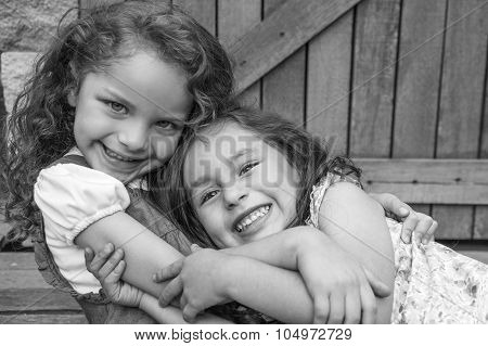 Adorable young brunette girls embracing hugging showing love and friendship, looking into camera bla